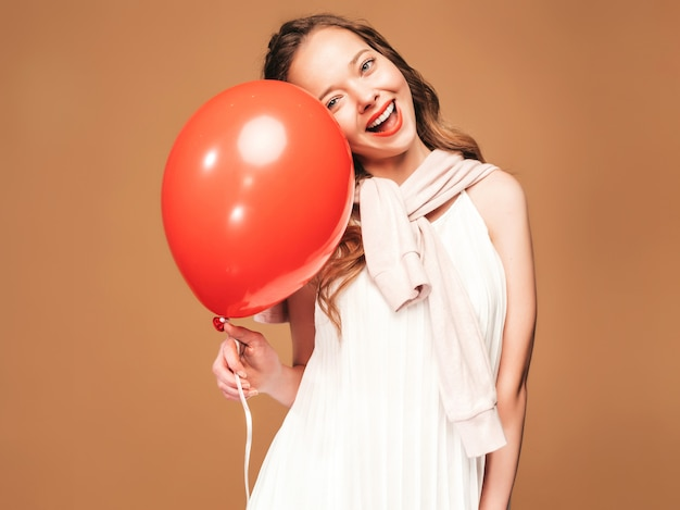 Podekscytowana Młoda Dziewczyna Pozuje W Modnej Letniej Białej Sukni. Kobieta Model Z Czerwony Balonik Pozowanie. Gotowy Na Imprezę Darmowe Zdjęcia