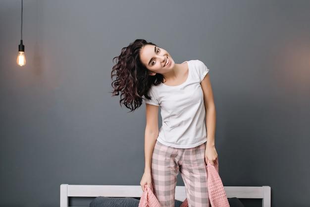 Podekscytowana Młoda Radosna Kobieta Z Kręconymi Włosami Brunetki W Piżamie, Zabawy Na łóżku. Uśmiechnięty, Wyrażający Prawdziwie Pozytywne Emocje, Relaksujący Się W Domu W Nowoczesnym Mieszkaniu Darmowe Zdjęcia