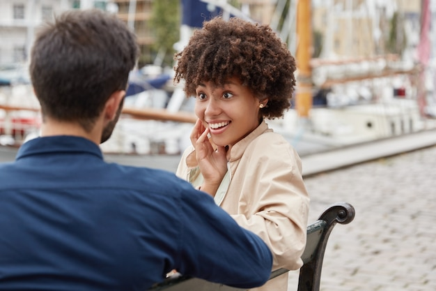 Podekscytowana Pozytywna śliczna Ciemnoskóra Kobieta Ma Przyjemny Uśmiech, Plotki Z Najlepszą Przyjaciółką, Darmowe Zdjęcia