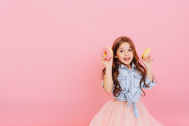 Podekscytowana Radosna Młoda ładna Dziewczyna W Tiulowej Spódnicy Wyrażająca Pozytywne Nastawienie, Zabawy Z Aparatem Z Pączkami Na Białym Tle Na Różowym Tle. Szczęśliwe Dzieciństwo Z Smacznym Deserem. Umieść Tekst Fot Darmowe Zdjęcia