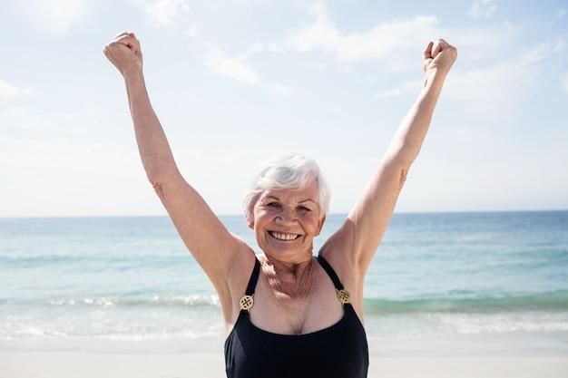 Podekscytowana Starsza Kobieta Stojąc Na Plaży Premium Zdjęcia