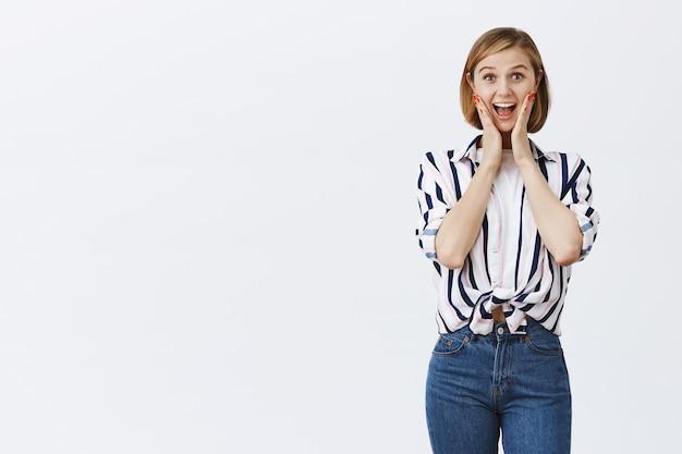 Podekscytowana Szczęśliwa Blond Dziewczyna Wyglądająca Na Rozbawioną I Zachwyconą Wspaniałą Wiadomością Darmowe Zdjęcia