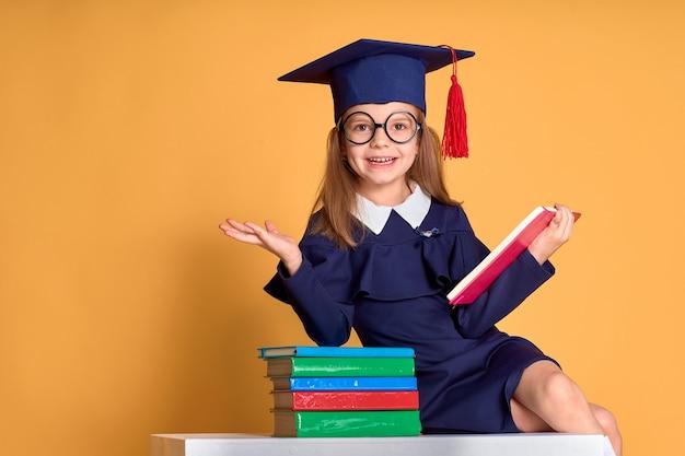 Podekscytowana Uczennica W Stroju Dyplomowym Studiująca Z Podręcznikami Premium Zdjęcia