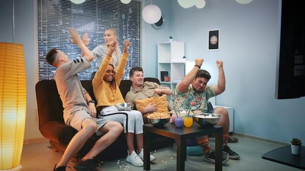 Podekscytowani Fani Oglądają Sport W Telewizji I Rozlewają Popcorn Premium Zdjęcia