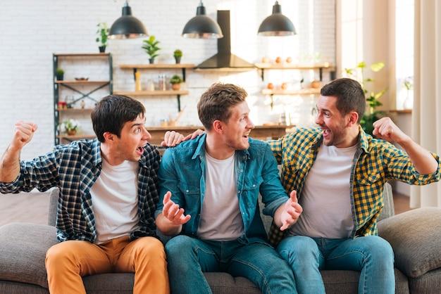 Podekscytowani młodzi mężczyźni siedzą na kanapie doping w domu Darmowe Zdjęcia