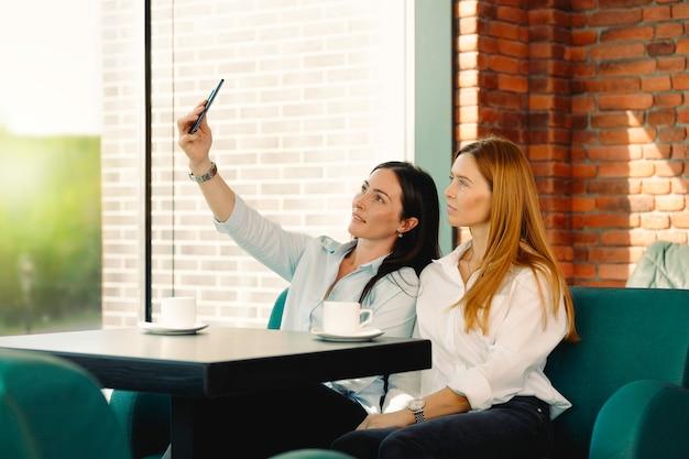 Podekscytowani Przyjaciele Robią Selfie Na Smartfonie, Bawiąc Się W Coffeeshopie. Uczniowie Z Uśmiechem Na Telefon Spotkali Się W Kawiarni. Dwie Młode Kobiety Biznesu Pozowanie Do Autoportretu W Przerwie Na Kawę W Biurze. Premium Zdjęcia