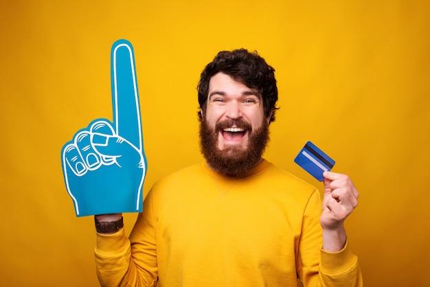 Podekscytowany Brodacz Trzyma Kartę Kredytową Lub Debetową I Ma Na Sobie Rękawicę Z Pianki. Premium Zdjęcia