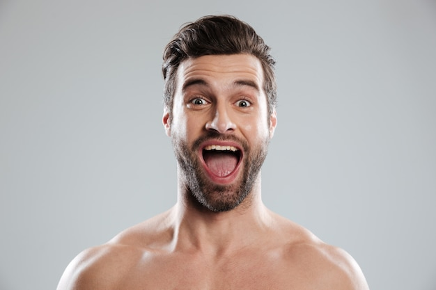 Podekscytowany Brodaty Mężczyzna Z Nagimi Ramionami I Otwartymi Ustami Darmowe Zdjęcia