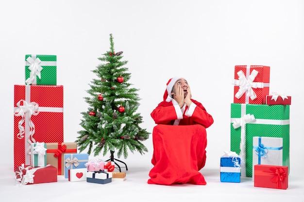 Podekscytowany Emocjonalnie Młody Mężczyzna Przebrany Za świętego Mikołaja Z Prezentami I Udekorowaną Choinką Na Białym Tle Materiału Filmowego Darmowe Zdjęcia