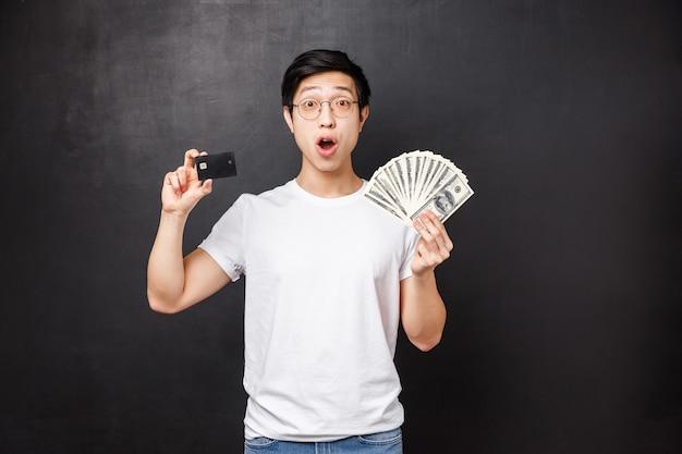 Podekscytowany I Zdumiony Bogaty Szczęśliwy Azjata Trzymający Dolary I Kartę Kredytową Z Zadziwionym Wyrazem Twarzy Premium Zdjęcia