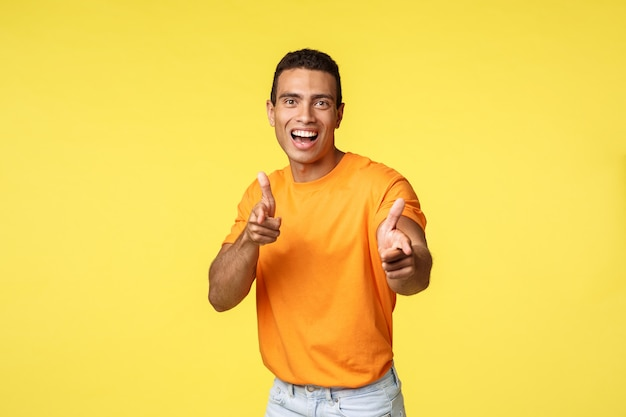Podekscytowany przyjazny i towarzyski młody przystojny facet w pomarańczowej koszulce Premium Zdjęcia