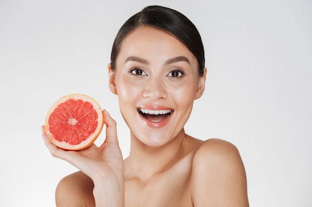 Podekscytowany Szczęśliwa Kobieta Ze Zdrową świeżą Skórą Gospodarstwa Soczystych Czerwonych Grejpfrutów I Patrząc Na Kamery Z Uśmiechem, Odizolowane Na Białym Darmowe Zdjęcia