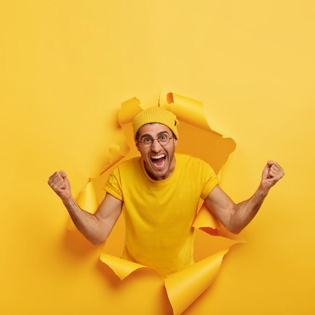 Podekscytowany Uszczęśliwiony Mężczyzna Pozuje Przez Podarty Papier Darmowe Zdjęcia