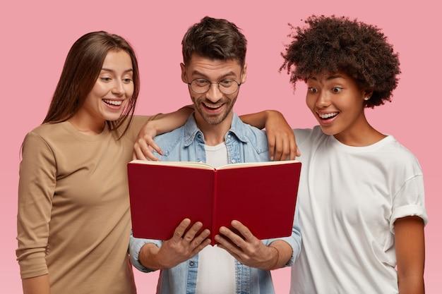Podekscytowany Wesoły Ciekawy Wieloetniczny Dwie Młode Kobiety I Przystojny Facet Patrzą Na Podręcznik, Czytają Informacje, Odizolowane Na Różowej ścianie. Zadowoleni Uczniowie Międzyrasowi Uczą Się Czegoś Przed Egzaminem Darmowe Zdjęcia