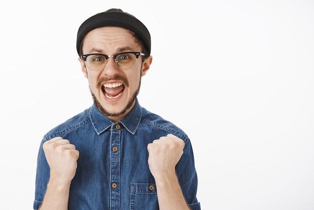 Podekscytowany Wiwatujący Nieogolony Model Mężczyzna Czuje Się Szczęśliwy I Triumfuje Unosząc Zaciśnięte Pięści I Krzycząc Wspierająco, Uśmiechając Się Szeroko Darmowe Zdjęcia