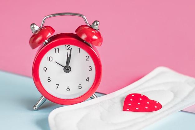 Podkładki Menstruacyjne, Czerwony Budzik Na Różowym Tle. Koncepcja Okresu Miesiączkowego. Koncepcja Opóźnienia Miesiączki Premium Zdjęcia