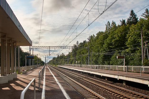 Podmiejska stacja kolejowa z szynami i peronami w dwóch kierunkach Premium Zdjęcia