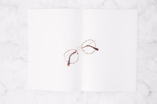 Podniesiony widok eyeglasses nad pustym białym papierem na marmurowym tle Darmowe Zdjęcia