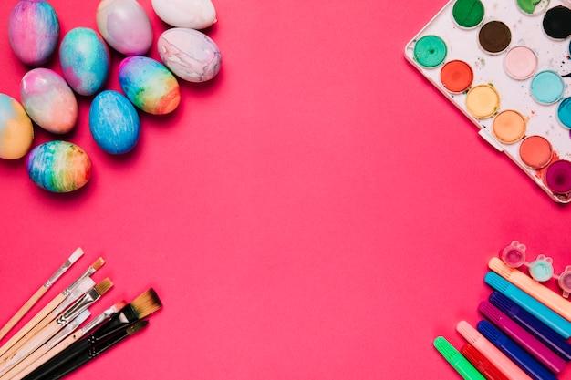 Podniesiony Widok Kolorowych Pisanek; Szczotki; Flamaster I Pudełko Akwarelowe Na Różowym Tle Darmowe Zdjęcia