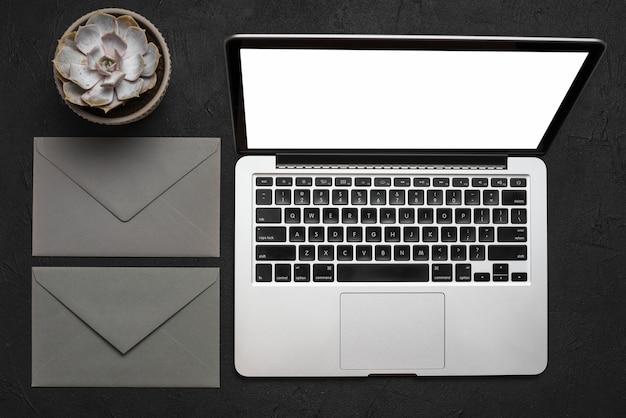 Podniesiony Widok Laptopa; Koperta I Soczyste Rośliny Na Czarnej Powierzchni Darmowe Zdjęcia