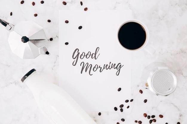 Podniesiony widok tekstu na dzień dobry na papierze; kafeteria dzbanek do kawy; filiżanka kawy; butelka mleka i ziarna kawy na tle marmuru Darmowe Zdjęcia