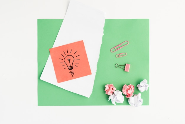 Podniesiony widok wyciągniętej żarówki i zmiętego papieru z spinaczem do papieru na zielonej karcie Darmowe Zdjęcia