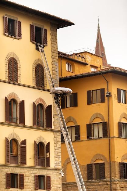 Podnoszenie ładunku Na Najwyższe Piętro Za Pomocą Dużych Schodów W Centrum Florencji, Włoch, Toskanii. Premium Zdjęcia