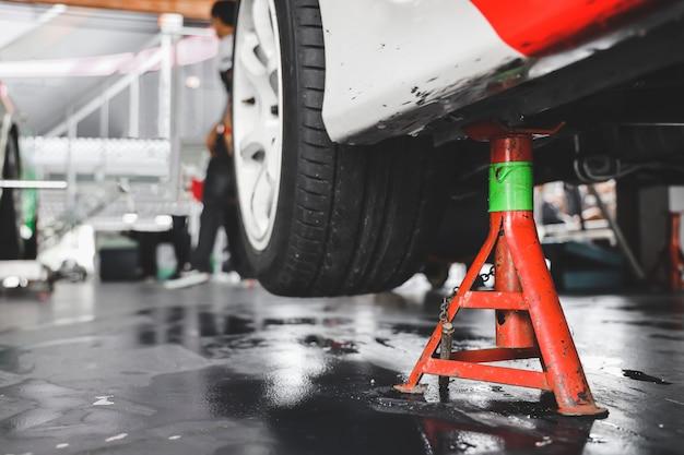 Podnoszenie samochodu do zmiany opon w garażu. Premium Zdjęcia
