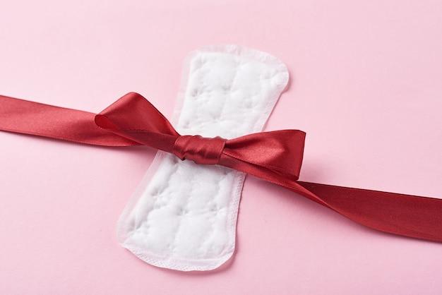 Podpaska Higieniczna I Czerwoną Wstążką Na Różowym Tle Premium Zdjęcia