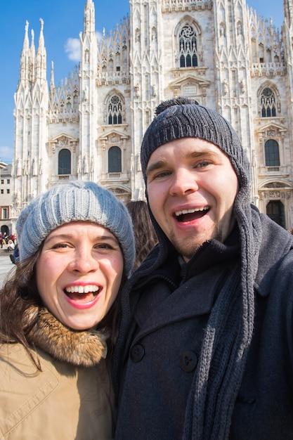 Podróże, Włochy I Koncepcja śmiesznej Pary - Szczęśliwi Turyści Biorący Autoportret Z Gołębiami Przed Katedrą Duomo W Mediolanie Premium Zdjęcia