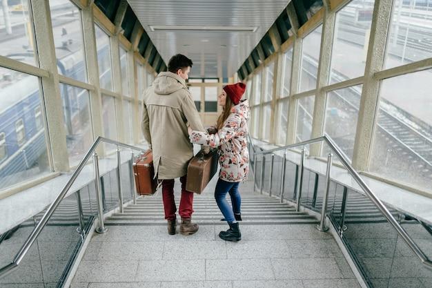 Podróżna Para Z Torbami Chodzi W Dół Schodki. Premium Zdjęcia