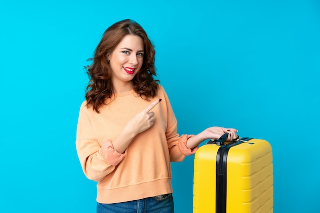 Podróżnicza kobieta wskazuje palec strona z walizką nad odosobnionym błękitnym tłem Premium Zdjęcia