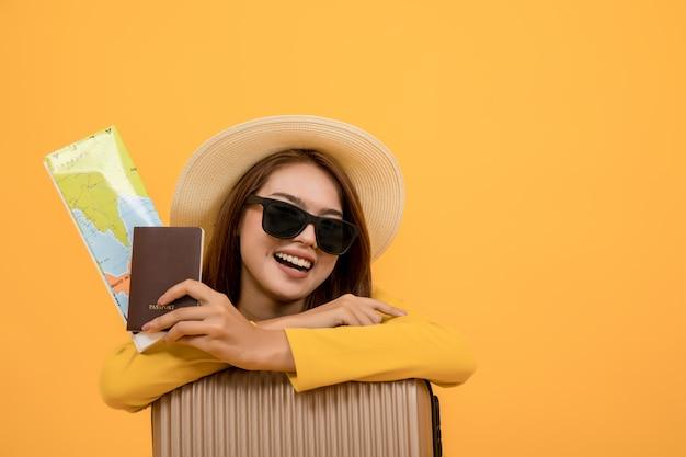 Podróżnicza Turystyczna Kobieta W Lat Przypadkowych Ubraniach, Kobiety Mienia Paszport Z Mapą, Kapelusz I Okulary Przeciwsłoneczni Daleko Od Odizolowywający Nad żółtym Tłem Premium Zdjęcia