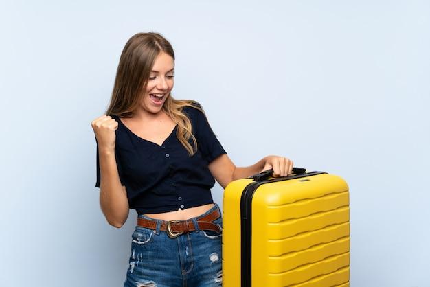 Podróżnik blondynki kobieta świętuje zwycięstwo z walizką Premium Zdjęcia