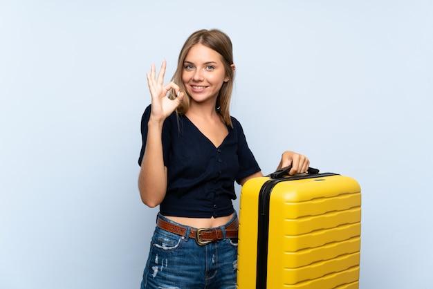 Podróżnik blondynki kobieta z walizką pokazuje ok znaka z palcami Premium Zdjęcia