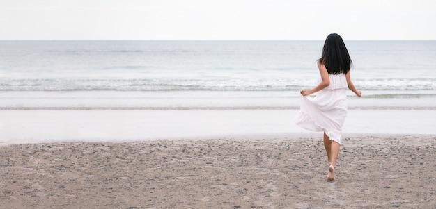 Podróżnik kobieta biegająca na morze plaży Premium Zdjęcia