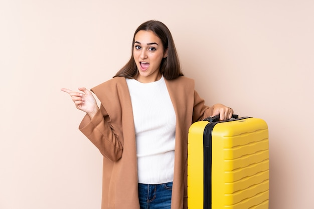 Podróżnik kobieta z walizką zaskoczony i wskazujący palec na bok Premium Zdjęcia