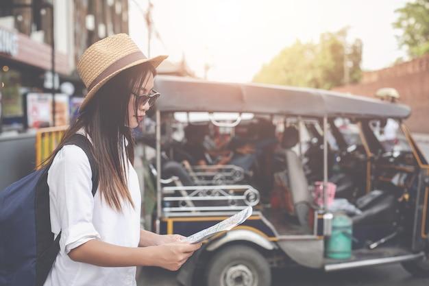 Podróżnik Młoda Kobieta Z Plecakiem Patrząc Trzymać Mapę W Stolicy. Dzień Turystyki. Premium Zdjęcia