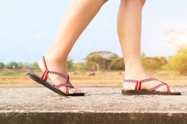 Podróżnik młode kobiety na sneakers kują odprowadzenie na moscie na słonecznym dniu Premium Zdjęcia