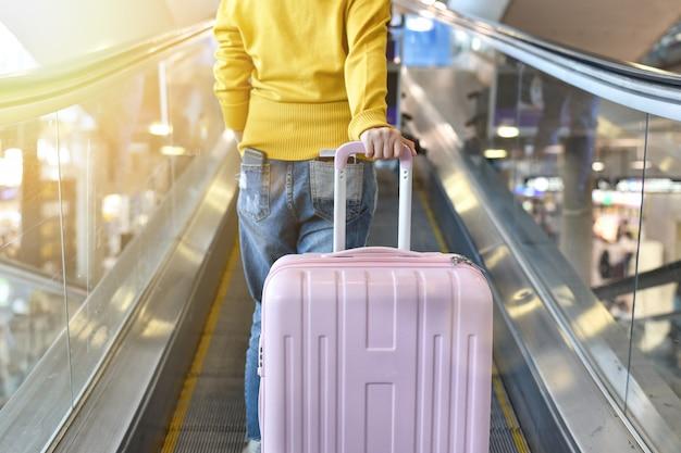 Podróżnik Niesie Dużą Walizkę Na Chodniku Schodów Ruchomych Na Lotnisku Premium Zdjęcia