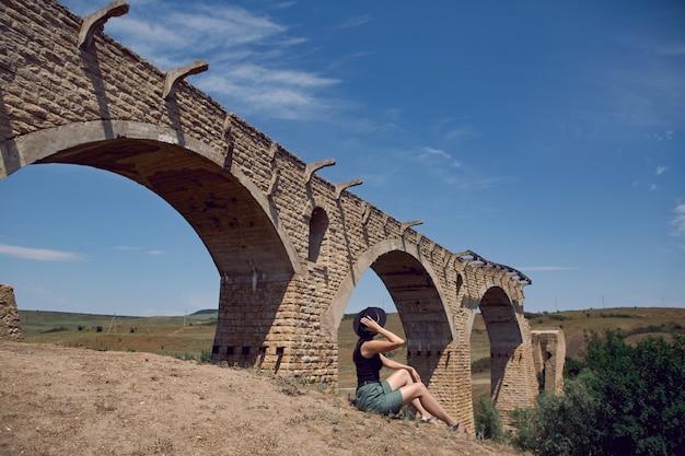 Podróżnik W Czarnym Kapeluszu Siedzi Latem Obok Zniszczonego Starego Kamiennego Mostu Premium Zdjęcia