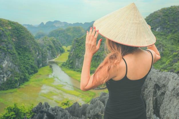 Podróżnik w wietnamie. młoda azjatykcia kobieta stoi na szczytowej jaskini mua. prowincja ninh binh, wietnam. Premium Zdjęcia