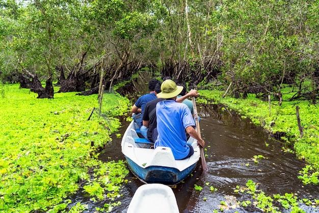 Podróżnik Zwiedza Tradycyjną łódź W Tra Su Lesie, Mekong Delty Podróż, Vietnam Premium Zdjęcia