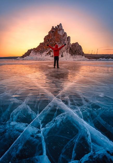 Podróżnika Mężczyzna Odzieży Czerwieni Ubrania I Dźwiganie Ręki Pozycja Na Naturalnym łamanie Lodzie W Zamarzniętej Wodzie Przy Wschodem Słońca W Jeziornym Baikal, Syberia, Rosja. Premium Zdjęcia