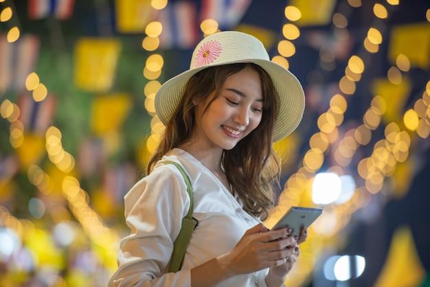 Podróżujący styl życia azjatycka dziewczyna z smartphone przy nocą Premium Zdjęcia