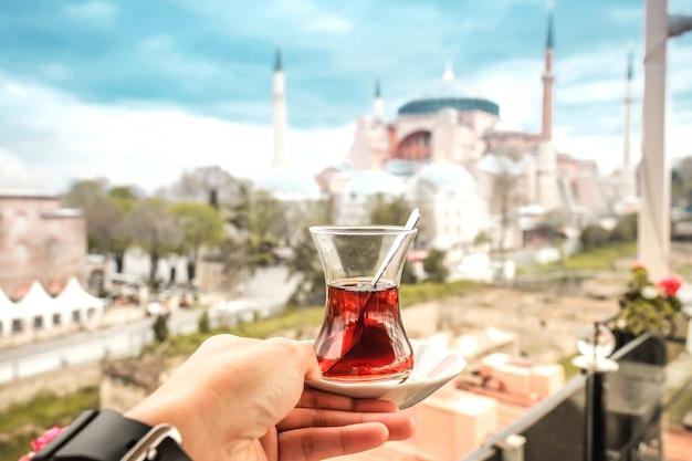 Podróżuje kobiety z tureckiej herbaty przyglądającym widokiem hagia sophia w istanbuł, turcja Premium Zdjęcia