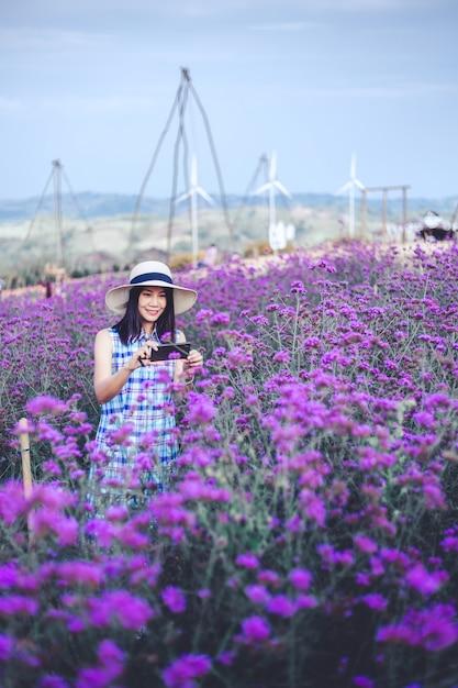 Podróży Kobieta Z Purpurowym Kwiatem Premium Zdjęcia