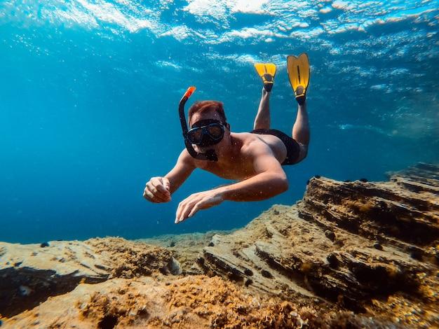 Podwodne zdjęcie mężczyzn nurkujących w wodzie morskiej Premium Zdjęcia