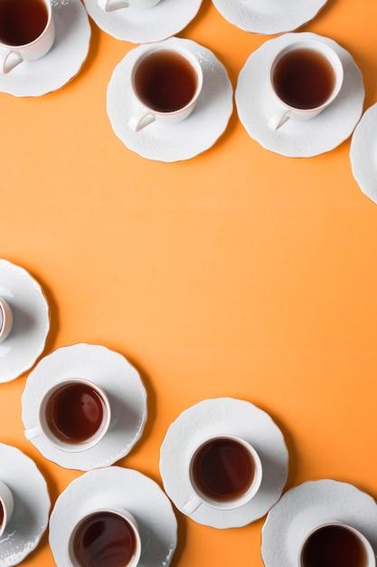 Podwyższony Widok Filiżanki Herbaty Ziołowe I Spodki Na Rogu Pomarańczowym Tle Darmowe Zdjęcia