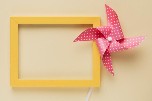 Podwyższony Widok Kropkowana Pinwheel I Kolor żółty Rama Na Beżowym Tle Darmowe Zdjęcia